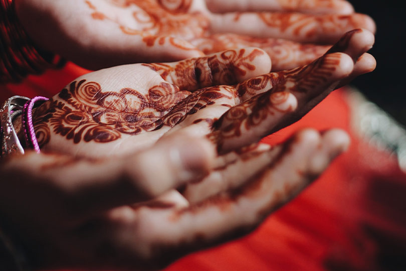 Women decorating their hand with Mehendi during Teej